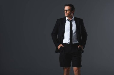 fashionable man with eyeglasses in shorts with hands in pockets looking away isolated on grey background