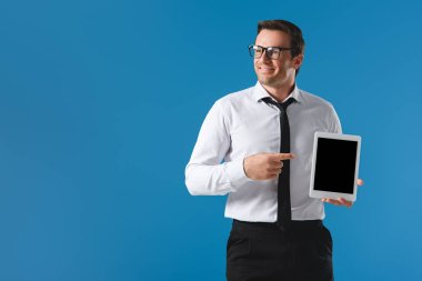 handsome smiling businessman pointing with finger at digital tablet with blank screen and looking away isolated on blue