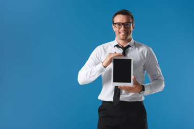 handsome man in eyeglasses holding digital tablet with blank screen and smiling at camera isolated on blue