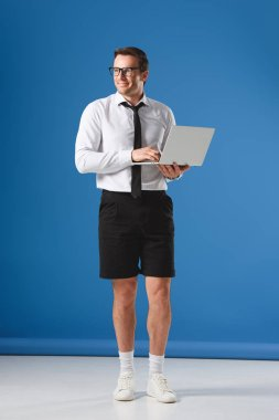 handsome smiling businessman in shorts using laptop and looking away on blue