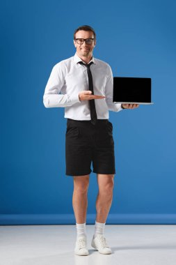 handsome businessman in shorts showing laptop with blank screen and smiling at camera on blue