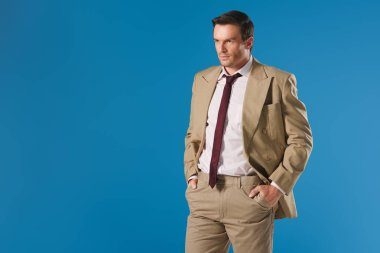 handsome man standing with hands in pockets and looking away isolated on blue