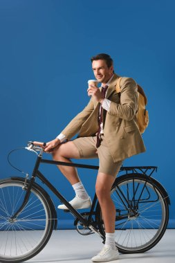 smiling man with coffee to go riding bicycle and looking away on blue