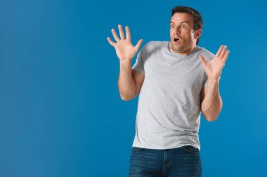 shocked man raising hands and looking away isolated on blue