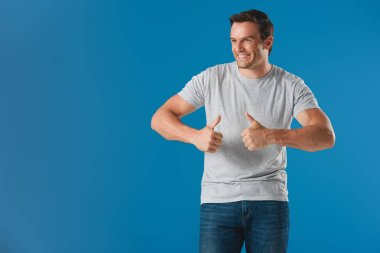 handsome smiling man showing thumbs up and looking away isolated on blue