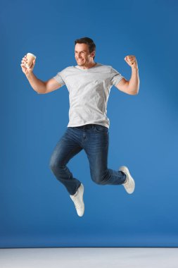 excited man with coffee to go jumping and triumphing on blue