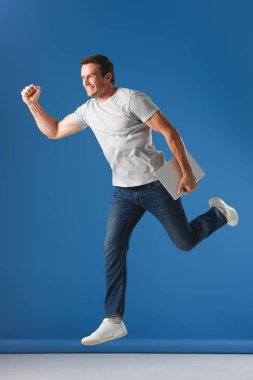 cheerful man holding laptop and jumping on blue