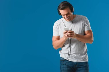 smiling man in headphones using smartphone isolated on blue