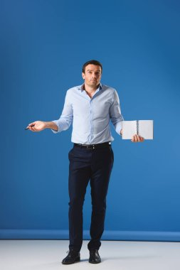 full length view of man holding blank notebook and looking at camera on blue