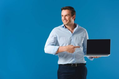 handsome smiling man pointing with finger at laptop with blank screen and looking away isolated on blue