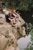 Fotografie high angle view of friends cyclists with backpacks resting with sport bottle of water and apple on rocky cliff near river in forest