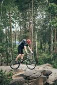 Fotografie muž extrémní cyklista v ochranné přilbě, jízda na horském kole v lese