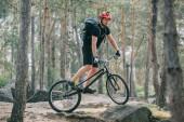 mladý muž extrémní cyklista v ochranné přilbě, jízda na horském kole v lese