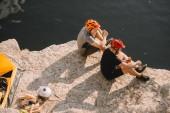 Védősisakok eszik utazók konzervek sátor, naplók, axe és sziklás sziklán üst közelében folyó felett