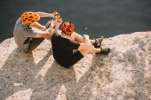 high angle view of male travelers in protective helmets clinking by cans on rocky cliff over river