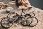 Fotografie oříznutý obraz mužské cestující sedí na zemi nedaleko kola, kotel, sekera a protokoly River