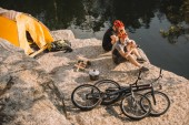 trial bikers resting near tent and cycles on rocky cliff over river