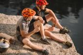 két férfi utazó eszik konzervek naplók, a fejsze és a üst sziklás sziklán közelében folyó felett