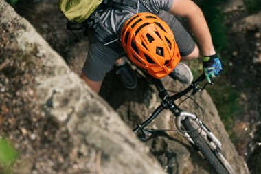 elevated view of male extreme cyclist in helmet riding on mountain bicycle