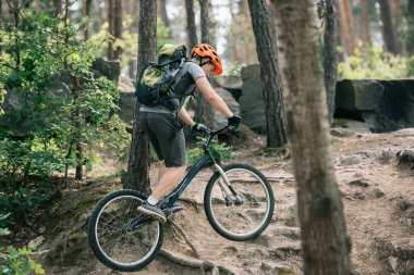 side view of male biker in helmet riding on bmx in forest