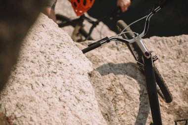 selective focus of mountain bike on rock and male extreme cyclist in helmet riding on bicycle behind