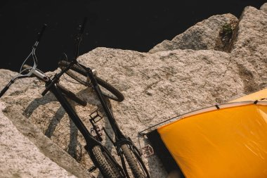 elevated view of mountain bicycles and tourist tent on rocky cliff over river