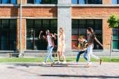 Fotografie glücklich multirassische Freunde mit langes Brett Spaß beim Zeit miteinander zu verbringen, auf Straße