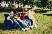 Fotografie smiling interracial friends resting on blue sofa together in park