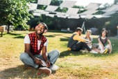 Photo selective focus of african american man in headphones with notebook resting on green grass with multiracial friends with laptop behind