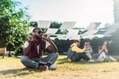 Fotografia messa a fuoco selettiva delluomo afroamericano in cuffie con il taccuino che riposa sullerba verde con gli amici multiracial con il computer portatile dietro