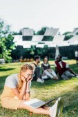 Photo selective focus of young smiling woman with laptop and multiracial friends behind resting on green grass in park