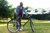 Fotografie smiling african american man with retro bicycle in park