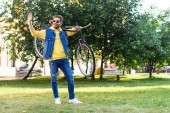 young cheerful man in sunglasses with retro bicycle greeting someone in park