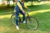 částečný pohled člověka stylové muže na koni retro kolo v parku