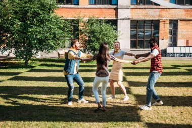 multicultural young friends holding hands while having fun together on summer day