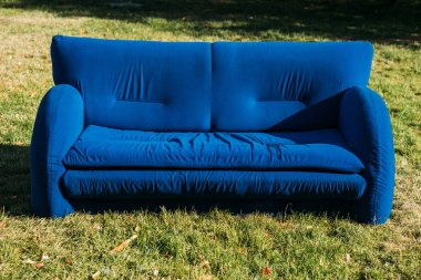 close up view of blue sofa standing on green lawn in park