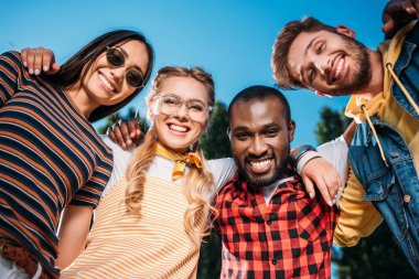 bottom view of smiling multiracial young friends looking at camera with blue sky on background