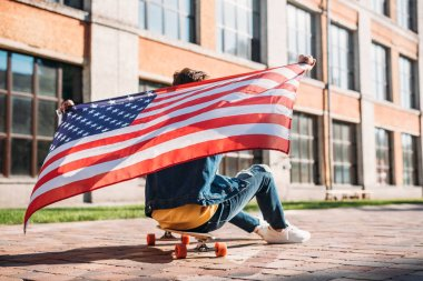 back view of man with american flag sitting on longboard on street
