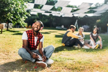 Selective focus of african american man in headphones with notebook resting on green grass with multiracial friends with laptop behind stock vector