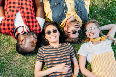 overhead view of happy multiethnic friends resting on green lawn together