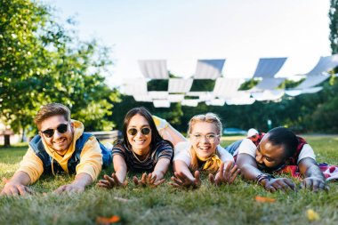 portrait of cheerful interracial young friends lying on green grass in park on summer day