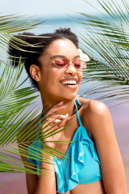 young smiling african american woman in sunglasses with flower in hair near palm leaves in front of sea