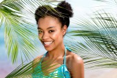 portrait of smiling african american woman near palm leaves in front of sea