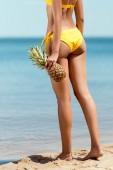 Fotografie ořízne obraz ženy v bikinách drží ananas na písečné pláži