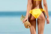 ořízne obraz ženy v bikinách drží ananas moře