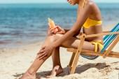 levágott kép nő alkalmazása fényvédő krém a bőr homokos strandon nyugágy ülve