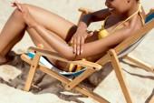 levágott kép alkalmazása fényvédő krém a bőr homokos strandon nyugágy ülve, fiatal nő