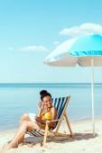 afrikai-amerikai nő, digitális tabletta, pihentető nyugágy és integetett kézzel tengerparton napernyő alatt