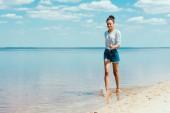 mladá usměvavá africká americká žena chůze v mořské vodě poblíž písčité pláže