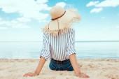 Fotografie zadní pohled na ženy v relaxační slamák na písečné pláži